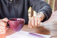 Woman checks the time on a wrist watch Stock Photos