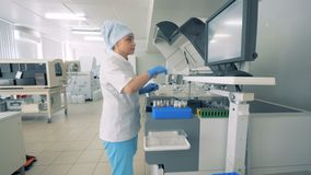 Woman scientist working in modern pharmacutical laboratory. A woman checks tubes with samples, typing on a machine screen in a room stock footage