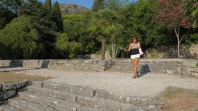 Woman Cheerfully Descends A Stone Staircase On A Background Hills And Palm Trees. Young cute brunette woman wearing a T-shirt, shorts and sandals. She happily stock video