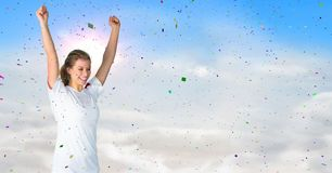 Woman cheering against sunny sky and confetti. Digital composite of Woman cheering against sunny sky and confetti Royalty Free Stock Image