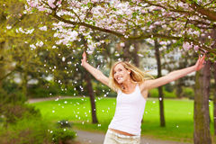 Woman cheering at cherry blossom Stock Photo