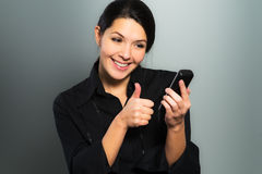 Woman cheering at good news on her mobile Royalty Free Stock Photography
