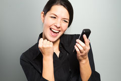 Woman cheering at good news on her mobile Royalty Free Stock Images