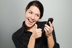 Woman cheering at good news on her mobile Stock Photography