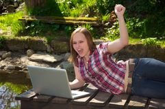Woman cheering with her laptop in the garden Stock Photography