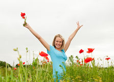 Woman cheering in the poppy field Stock Photography