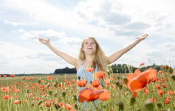 Woman cheering in poppy field Stock Photography