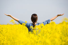 Woman cheering in the rape field Stock Image