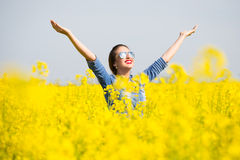 Woman cheering in the rape field Stock Photography
