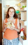 Woman  with cheese near refrigerator Stock Images