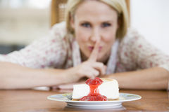 Woman With Cheesecake. Woman Tempted By Slice Of Strawberry Cheesecake royalty free stock images