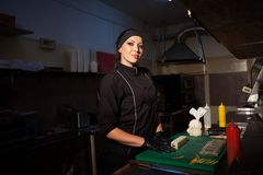Woman chef iprepares sushi restaurant in the kitchen. Woman chef in black clothing prepares sushi restaurant in the kitchen Stock Photography