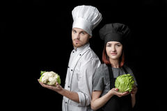 Woman chef in black uniform and man chef In white uniform hold Fresh green cabbage and cauliflower on  black background Royalty Free Stock Photos