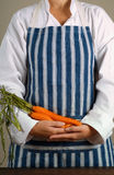 Woman chef with carrots Royalty Free Stock Photography