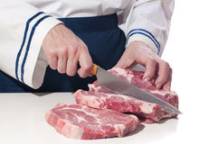 Woman chef cuts the meat. Royalty Free Stock Photography