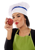 Woman chef eating red apple Stock Photos