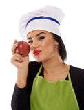 Woman chef eating red apple Royalty Free Stock Image
