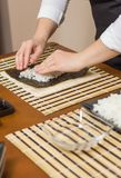 Woman chef filling japanese sushi rolls with rice Stock Photo