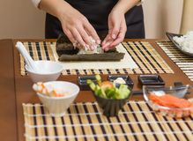 Woman chef filling japanese sushi rolls with rice Stock Photos