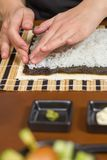 Woman chef filling japanese sushi rolls with rice Royalty Free Stock Photos