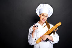 Woman chef with french bread and wine glass over dark background Stock Photography