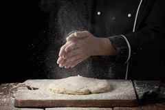 Woman chef hand clap with splash of white flour on a black background.  Stock Images