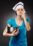 Woman chef holding a pot showing the ok hand sign of perfection. Studio shot of a woman chef holding a pot showing the ok hand sign of perfection over gray Stock Photos