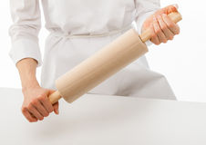 Woman chef holding rolling pin over white table Royalty Free Stock Photos