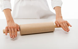 Woman chef holding rolling pin over white table Royalty Free Stock Photography