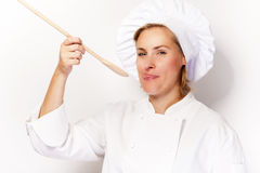 Woman chef holding a spoon and tasting from spoon. On white back Royalty Free Stock Images