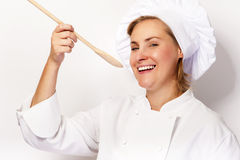 Woman chef holding a spoon and tasting from spoon. On white back Royalty Free Stock Photo
