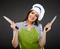 Woman chef holding two knives Royalty Free Stock Photography