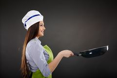 Woman chef holding a wok pan Royalty Free Stock Photo