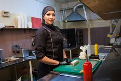 Woman chef iprepares sushi restaurant in the kitchen. Woman chef in black clothing prepares sushi restaurant in the kitchen Royalty Free Stock Images