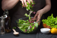 Woman chef in the kitchen cooking vegetable salad. Healthy Eating. Diet Concept. A Healthy Way Of Life. Cook At Home. To. Prepare The Food. Girl mixing salad Stock Photos