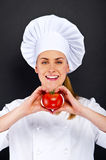 Woman chef make hand heart sign with tomato over dark background Royalty Free Stock Photos