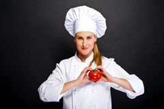 Woman chef make hand heart sign with tomato over dark background Stock Images