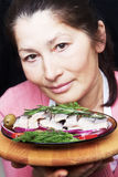 Woman chef offers a dish of smoked mackerel. On the dish with vegetables Royalty Free Stock Photography