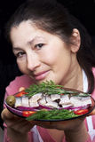 Woman chef offers a dish of smoked mackerel. On the dish with vegetables Royalty Free Stock Image