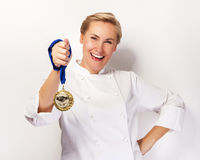 Woman in chef outfit and first prize medal smiling. Stock Photo