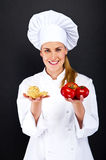 Woman chef over dark background with tomatos and pasta noodles Royalty Free Stock Photo