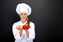 Woman chef over dark background with tomatos and pasta noodles Stock Photos