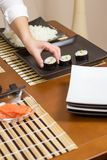 Woman chef placing japanese sushi rolls on a tray Stock Photography