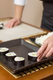 Woman chef placing japanese sushi rolls on a tray Stock Photos