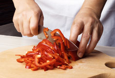 Woman chef prepares red peppers in the kitchen. Stock Image
