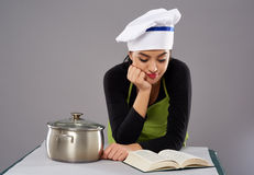 Woman chef reading recipe Stock Photography