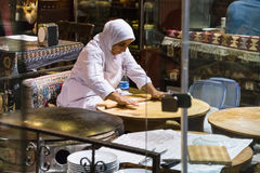 Woman chef rolls the dough with a rolling pin Stock Images