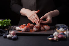 Woman chef rubs her paprika with fresh raw chicken drumsticks on a dark background. Nearby lie the ingredients for. Cooking: shallots, blue plums, garlic pepper Stock Photography