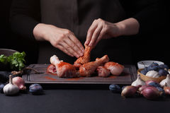 Woman chef rubs salt with fresh raw chicken drumsticks on a dark background. Nearby lie the ingredients for cooking. Shallots, blue plums, garlic pepper, salt Stock Image