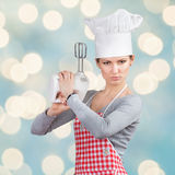 "Woman in chef's hat ""firing a gun"" with the mixer Stock Photo"